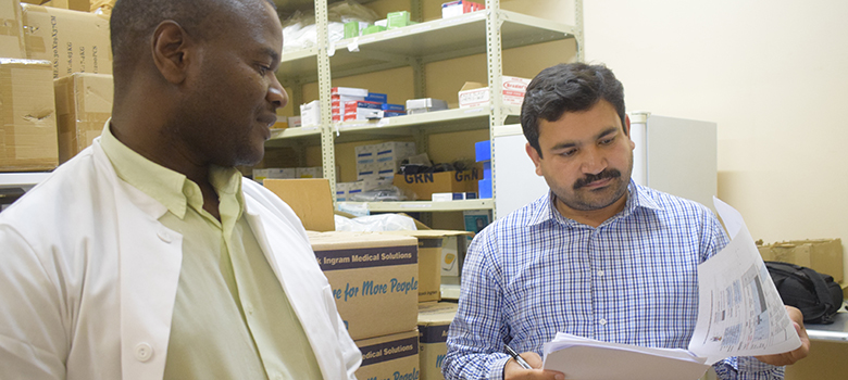 Two men stand in a pharmacy storeroom looking over papers.