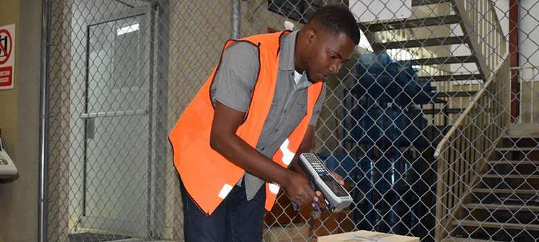 A man in an orange vests holds a barcode scanner up to a box in a warehouse.