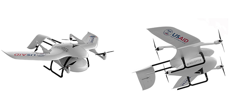 Two unmanned aerial vehicles emblazoned with the USAID and Wingcopter logos