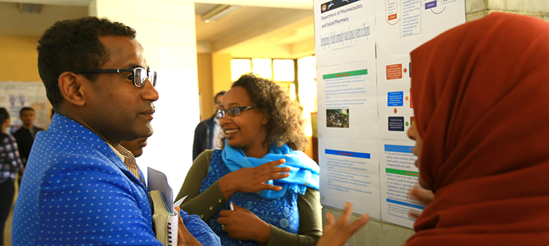 A man and woman stand in front of a poster conversing.