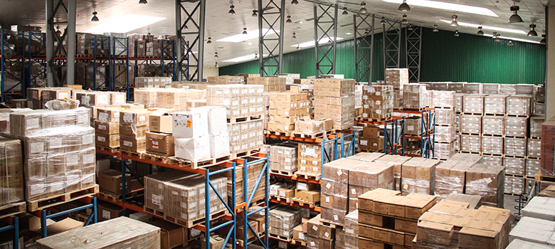 A large, brightly lit warehouse with cardboard boxes stacked high on pallets.