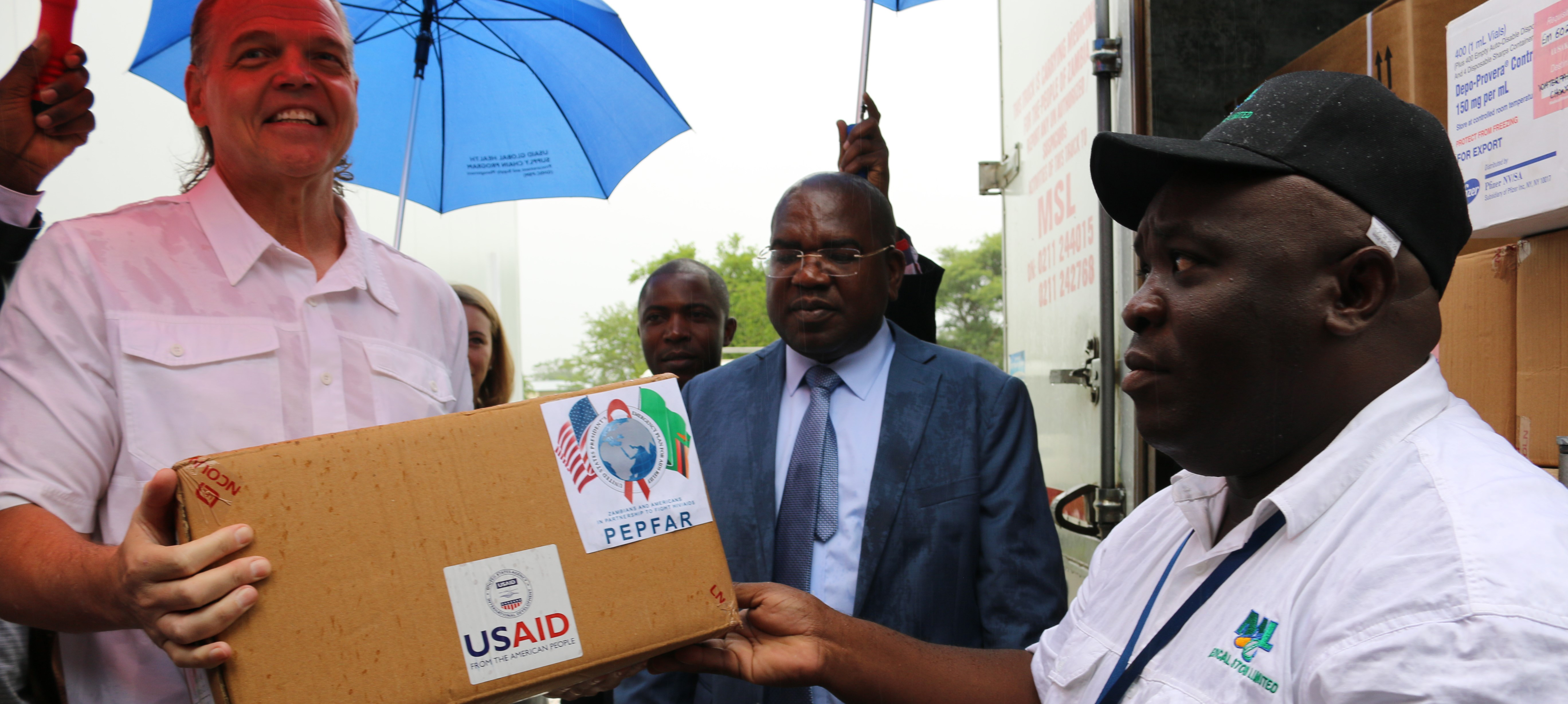 Ambassador Daniel Foote offloads a box of health commodities to be moved into a pre-fabricated storage unit as Zambian Minister of Health Chilufya and MSL Managing Director Chikuta Mbewe look on.