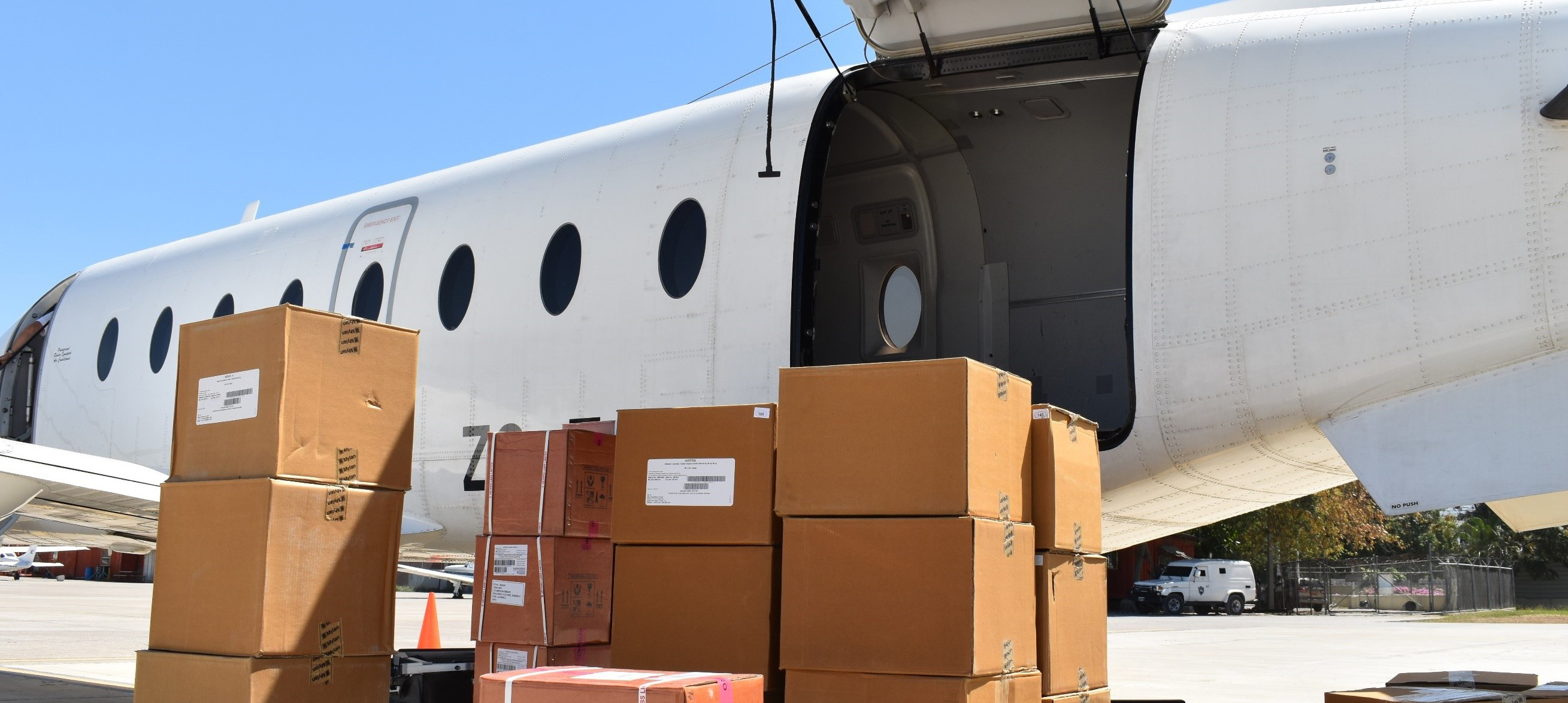 boxes sit in front of airplane for loading