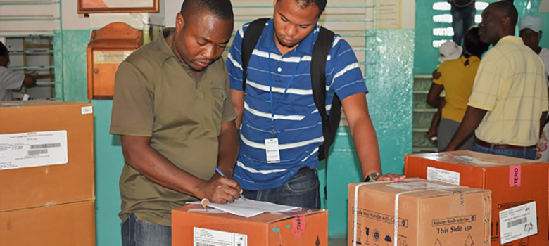 Workers in Haitian health facility verify delivery of ARVs surrounded by boxes of commodities