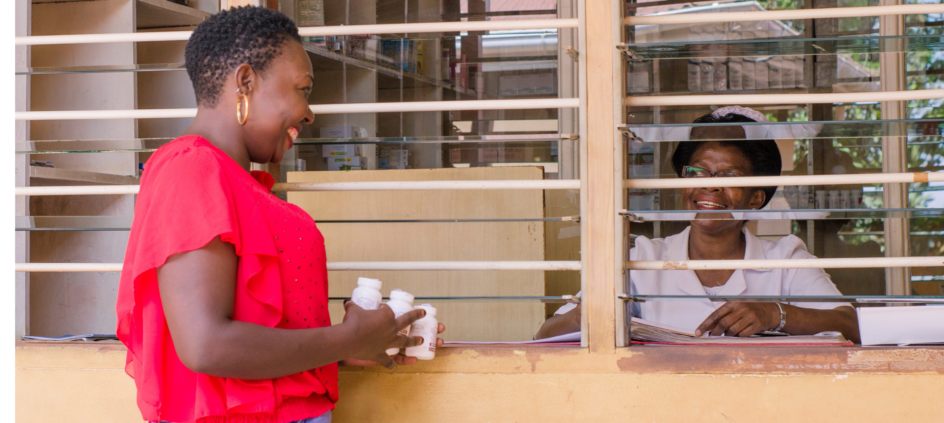 female patient holds bottles of medication as she talks with female pharmacist at health facility dispensing window