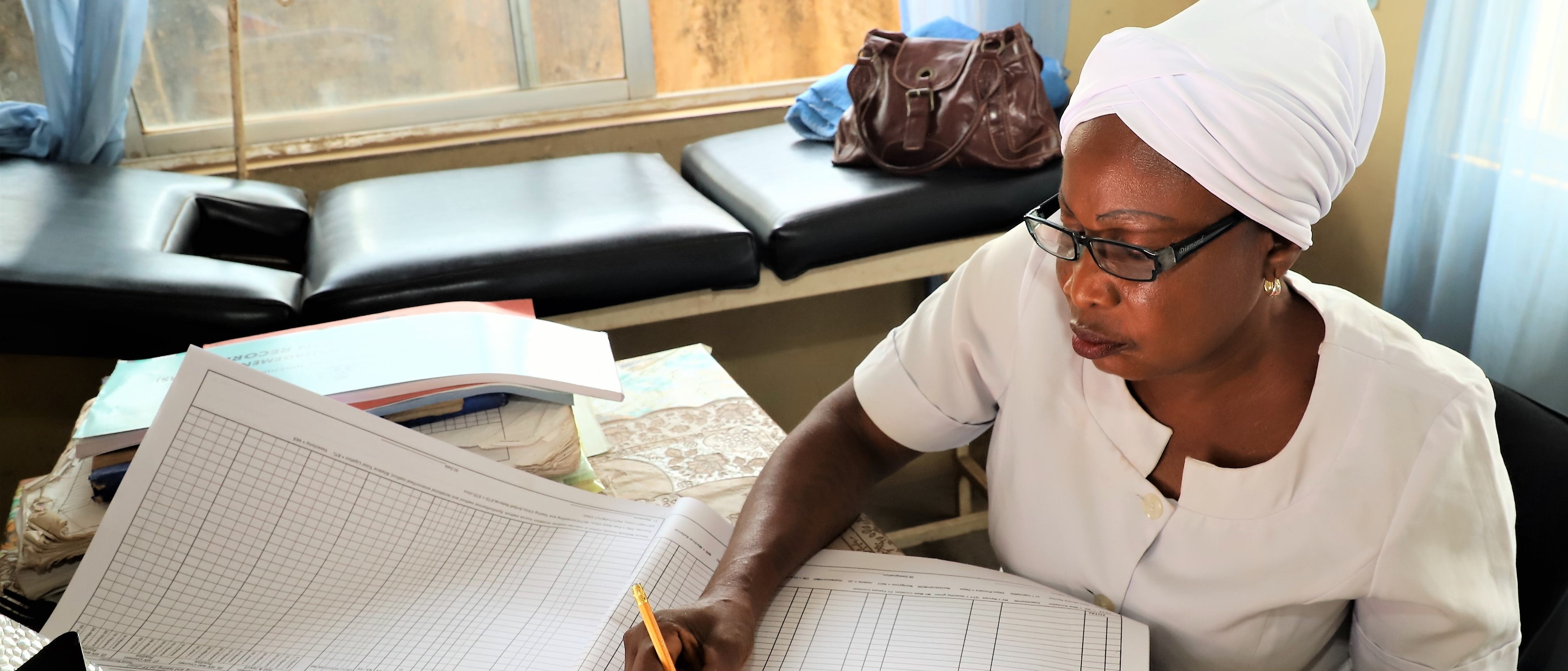 Nurse Anike fills out a family planning register at Apata health facility in Nigeria