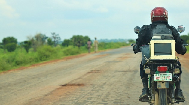 Image of a person on a motorcycle carrying lab samples in Nigeria.