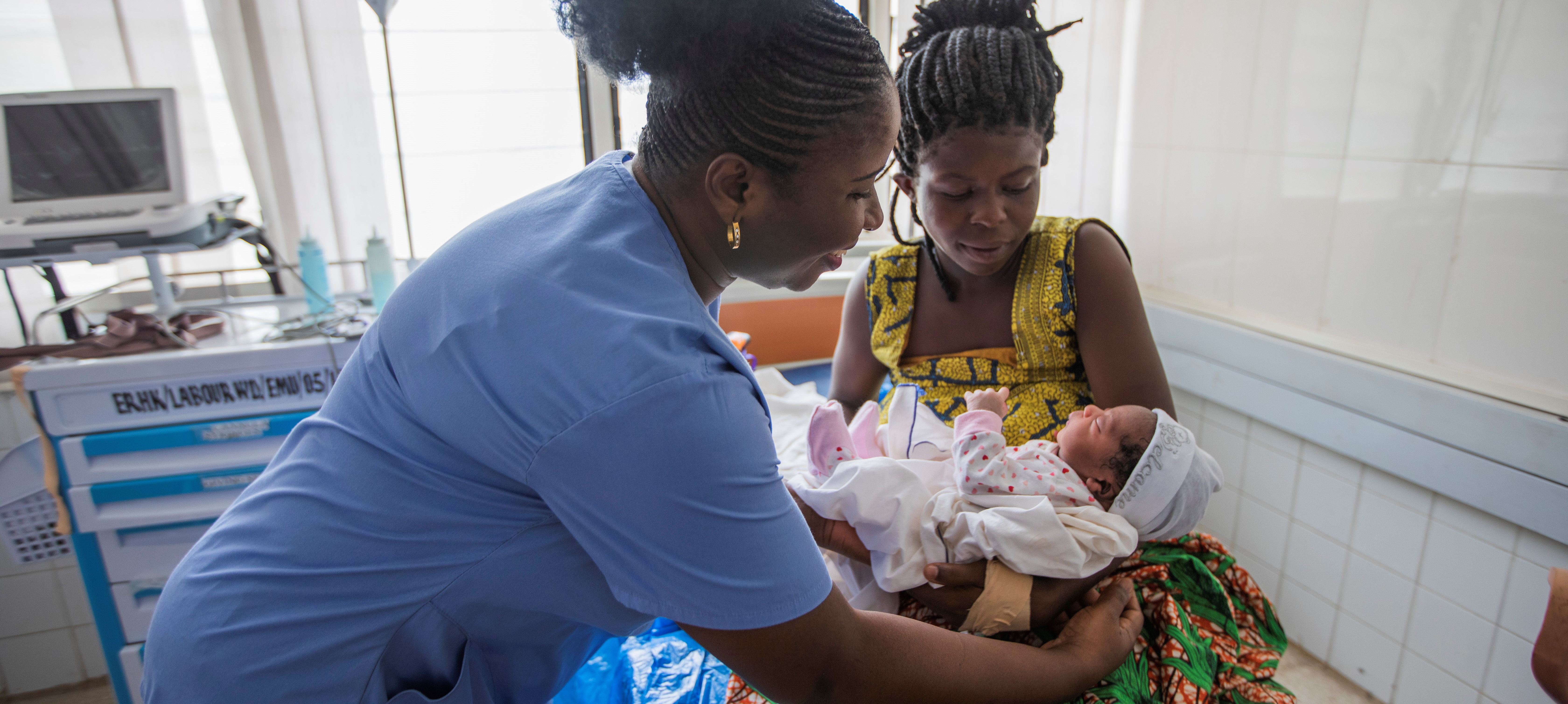Ghanaian Doctor hands newborn baby to mother on hospital bed
