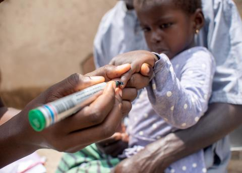 A child in Ghana has her finger marked with black ink to indicate that she received her dose of SPAQ.