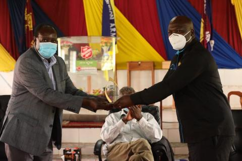 H.E. Governor Ottichillo presents overall best supply chain management performance award to a health worker.