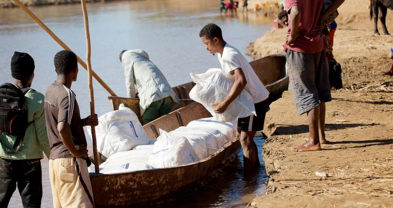 Men load insecticide-treated nets onto a boat.